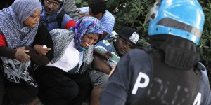"""Italian police officers surround a group of migrants with their arms linked together during an operation to remove them from the Italian-French border in the Italian city of Ventimiglia on June, 16, 2015.  Italy and France engaged in a war of words as a standoff over hundreds of Africans offered a graphic illustration of Europe's migration crisis. Italian Interior Minister Angelino Alfano described images of migrants perched on rocks at the border town of Ventimiglia after being refused entry to France as a """"punch in the face for Europe.""""  AFP PHOTO / JEAN CHRISTOPHE MAGNENET        (Photo credit should read JEAN CHRISTOPHE MAGNENET/AFP/Getty Images)"""
